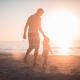 pai andando com filho na praia nos dias de visitação